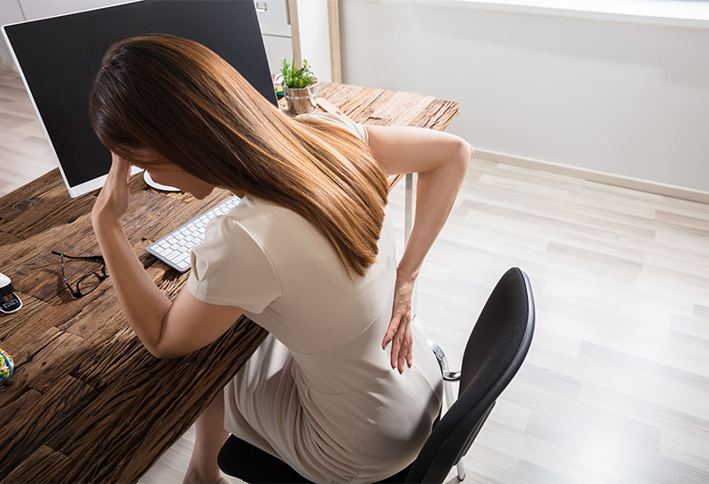 woman having back pain at work