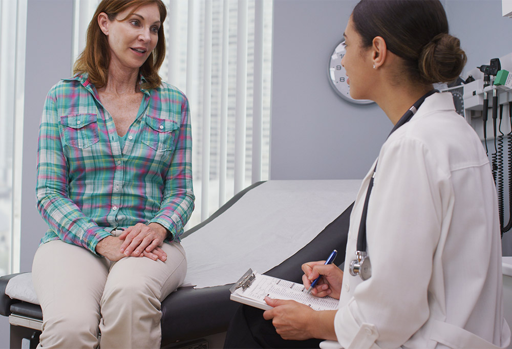 Attractive mid aged woman consulting with young doctor about health condition